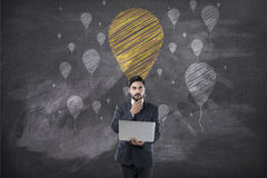 Businessman holding laptop in front of blackboard with balloon Royalty Free Stock Images