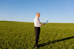 Businessman Holding Laptop On Grassy Field Against Sky Stock Images
