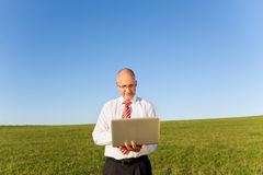 Businessman Holding Laptop On Grassy Field Stock Image