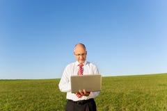 Businessman Holding Laptop On Grassy Field Stock Image
