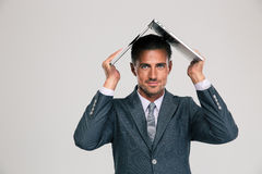 Businessman holding laptop on his head Royalty Free Stock Photos