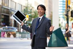 Businessman holding laptop and laughing. Portrait of successful businessman holding laptop and laughing Royalty Free Stock Images
