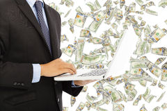 Businessman holding a laptop with money rain Royalty Free Stock Image