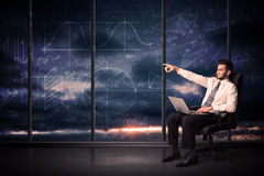Businessman holding laptop in office room with graph charts on w Royalty Free Stock Images