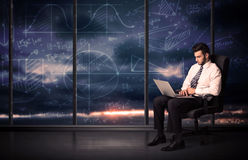 Businessman holding laptop in office room with graph charts on w Royalty Free Stock Image