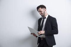 Businessman holding a laptop. Portrait of a cheerful bearded young businessman standing near a white wall and working with his laptop. Mock up Royalty Free Stock Photo