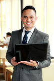 Businessman holding a laptop Stock Images