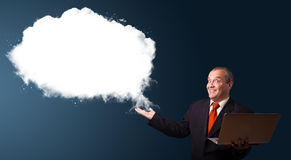 Businessman holding a laptop and presenting abstract cloud copy Royalty Free Stock Image