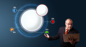 Businessman holding a laptop and presenting abstract modern pie Stock Photo