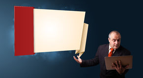 Businessman holding a laptop and presenting modern origami copy Royalty Free Stock Images