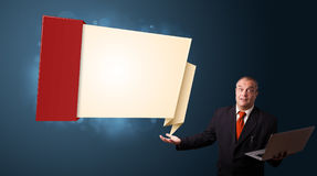 Businessman holding a laptop and presenting modern origami copy Royalty Free Stock Image