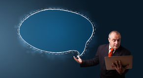 Businessman holding a laptop and presenting speech bubble copy s Stock Images