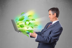 Businessman holding laptop with recycle and environmental symbo Stock Photography