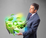Businessman holding laptop with recycle and environmental symbo Royalty Free Stock Photos