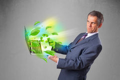 Businessman holding laptop with recycle and environmental symbo Stock Photos