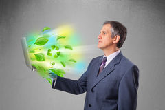 Businessman holding laptop with recycle and environmental symbo Royalty Free Stock Photo