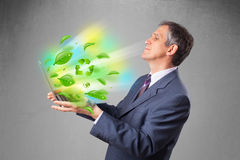 Businessman holding laptop with recycle and environmental symbo Stock Images