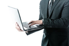 Businessman holding a laptop and typing Stock Photography