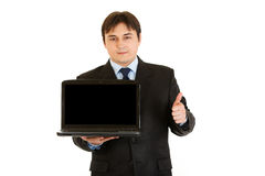 Businessman holding laptops and showing thumbs up Stock Image