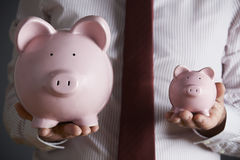 Businessman Holding Large And Small Piggy Bank Stock Image