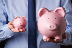 Businessman Holding Large And Small Piggy Bank Stock Photos