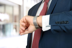 Businessman  holding leather briefcase checking time on his watch at office. Businessman holding leather briefcase checking time on his watch at office Stock Photography