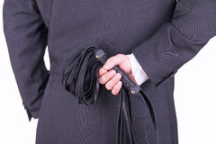 Businessman holding a leather whip. Royalty Free Stock Image