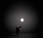 Businessman holding light bulb Stock Images