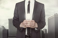 Businessman holding light bulb in hands. On cityscape background Royalty Free Stock Photos