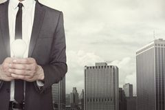 Businessman holding light bulb in hands. On cityscape background Royalty Free Stock Images