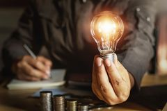 Businessman holding light bulb with money stack.saving energy power concept. Account, accounting, background, bright, creative, creativity, design, digital royalty free stock photos