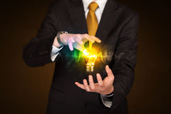 Businessman holding light bulb Stock Photo