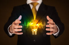 Businessman holding light bulb Stock Image