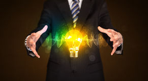 Businessman holding light bulb Royalty Free Stock Images