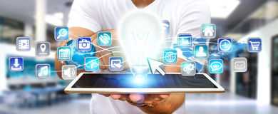 Businessman holding lightbulb with digital icons Stock Images