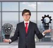 Businessman holding lightbulb gears. Businessman in office holding gears in form lightbulb Royalty Free Stock Images