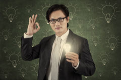 Businessman holding lightbulb and showing ok gesture Stock Photo