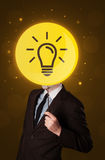 Businessman holding lightbulb sign. Smart businessman holding round sign with yellow lightbulb Royalty Free Stock Photography