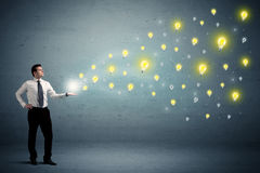 Businessman holding lightbulbs Stock Images