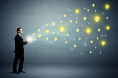 Businessman holding lightbulbs Stock Photography