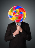 Businessman holding a lollipop Stock Photo