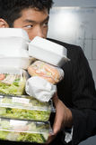Businessman holding lots of food Stock Image