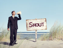 Businessman Holding loudspeaker with Signboard on Beach.  Royalty Free Stock Photo