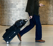 Businessman holding luggage. And using mobile phone Stock Image