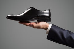 Businessman holding luxury leather shoes in hand. Stock Photography