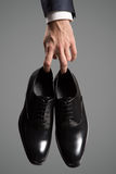 Businessman holding luxury leather shoes in hand. Stock Photo
