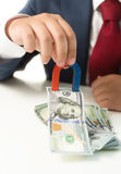 Businessman holding magnet and drawing money from the table Stock Photography
