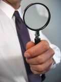 Businessman Holding Magnifying Glass. Close up view of a businessman in a white shirt and tie, holding a magnifying glass in one hand Stock Photo