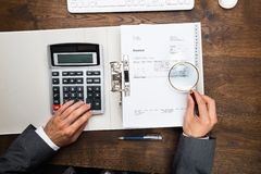 Businessman Holding Magnifying Glass Over Invoice Royalty Free Stock Photography