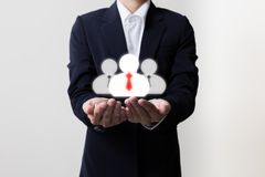 Businessman holding managers and team symbols Stock Image